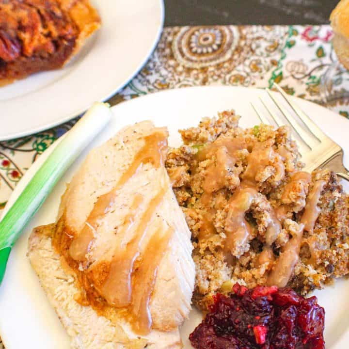 Cornbread dressing, turkey and cranberry sauce on white plate