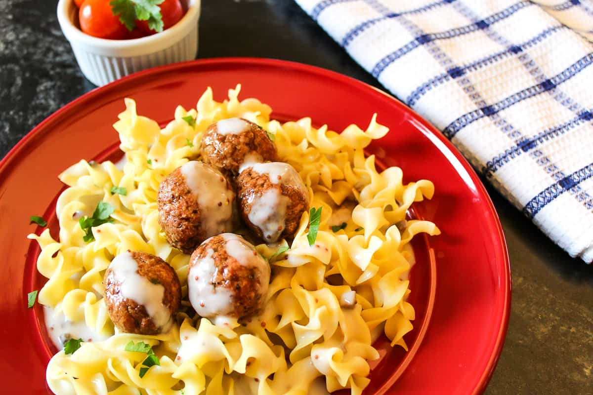 Swedish meatballs and sauce over egg noodles on red plate