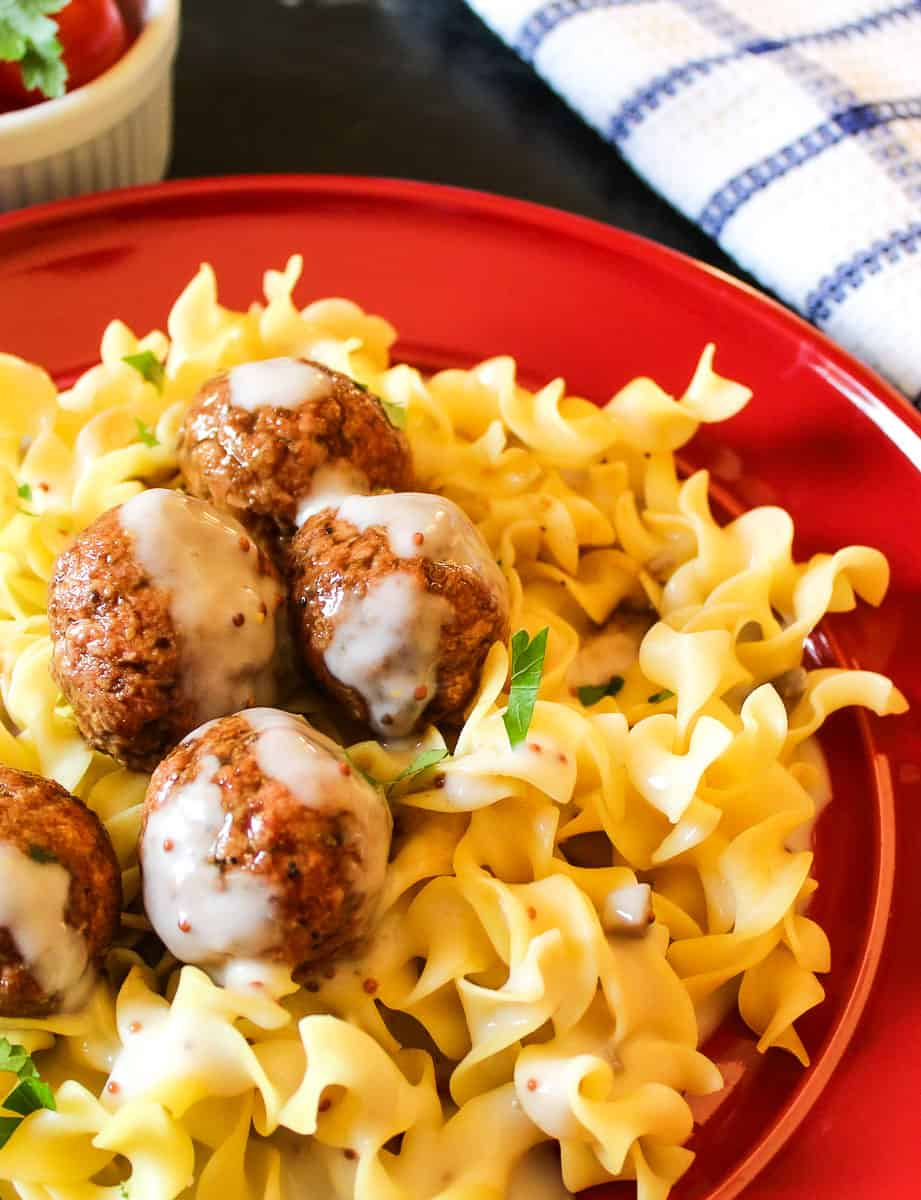Swedish meatballs with sauce over egg noodles on red plate