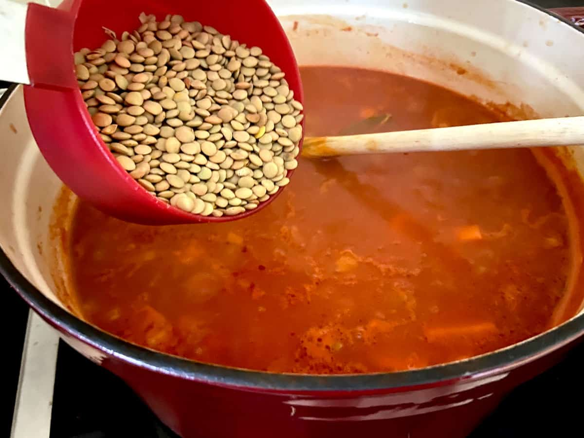 A cup of brown lentils being added to soup