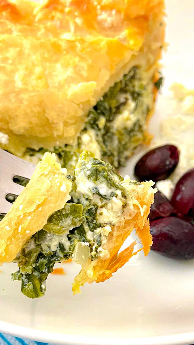 Fork holding a bit of spinach feta pie over white plate.