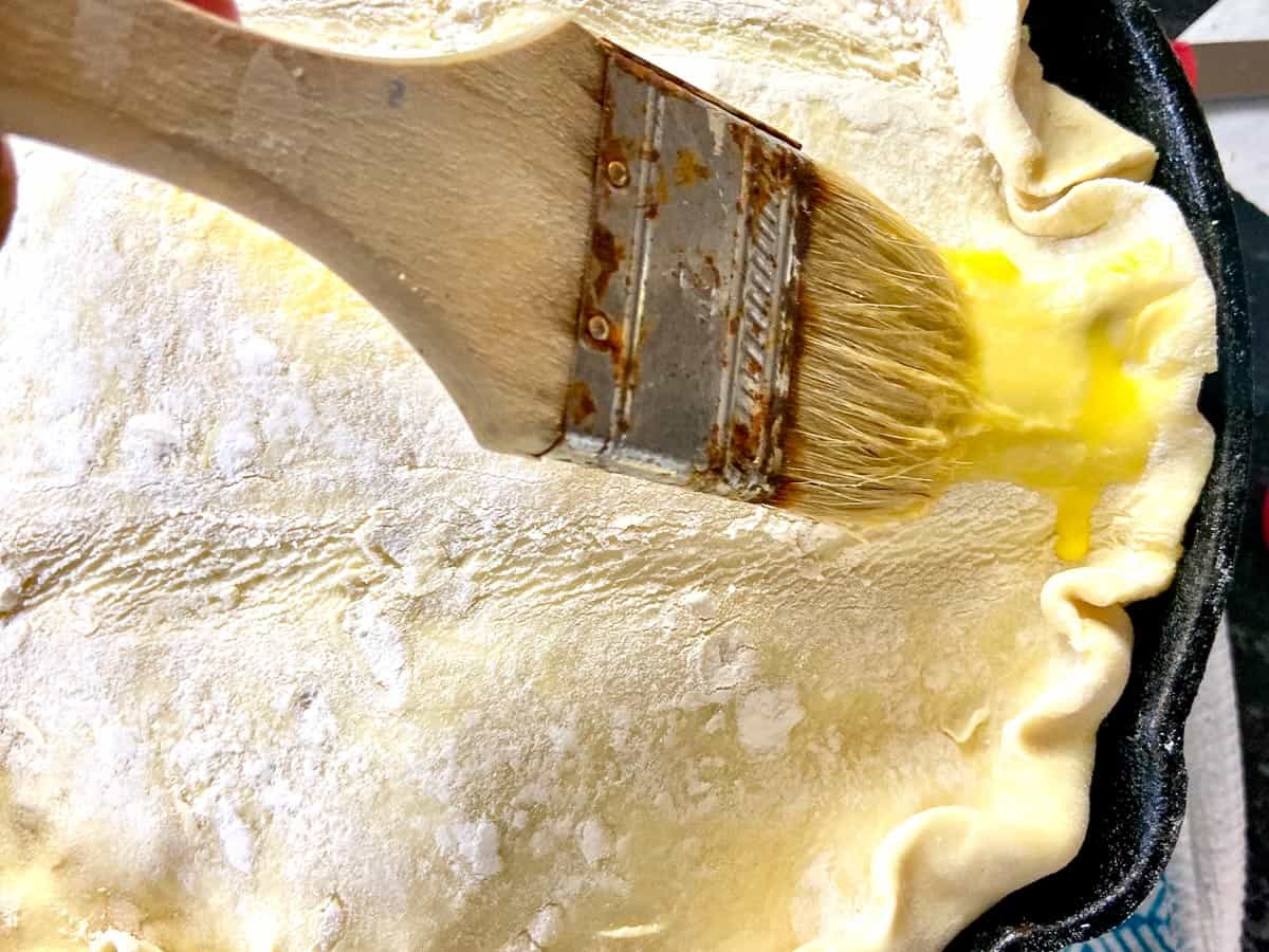 Egg wash being applied with pastry brush to puff pastry topping