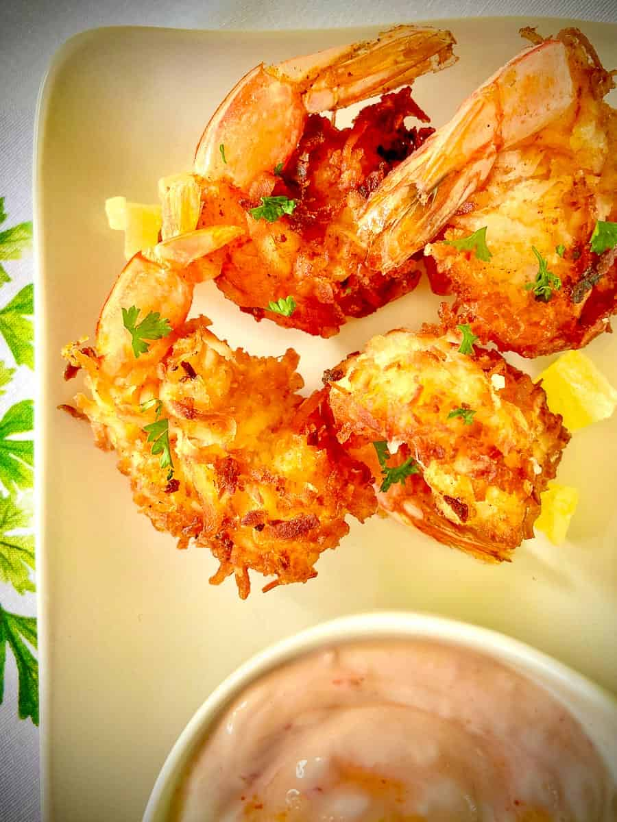 Coconut Shrimp on platter with a side of dipping sauce.