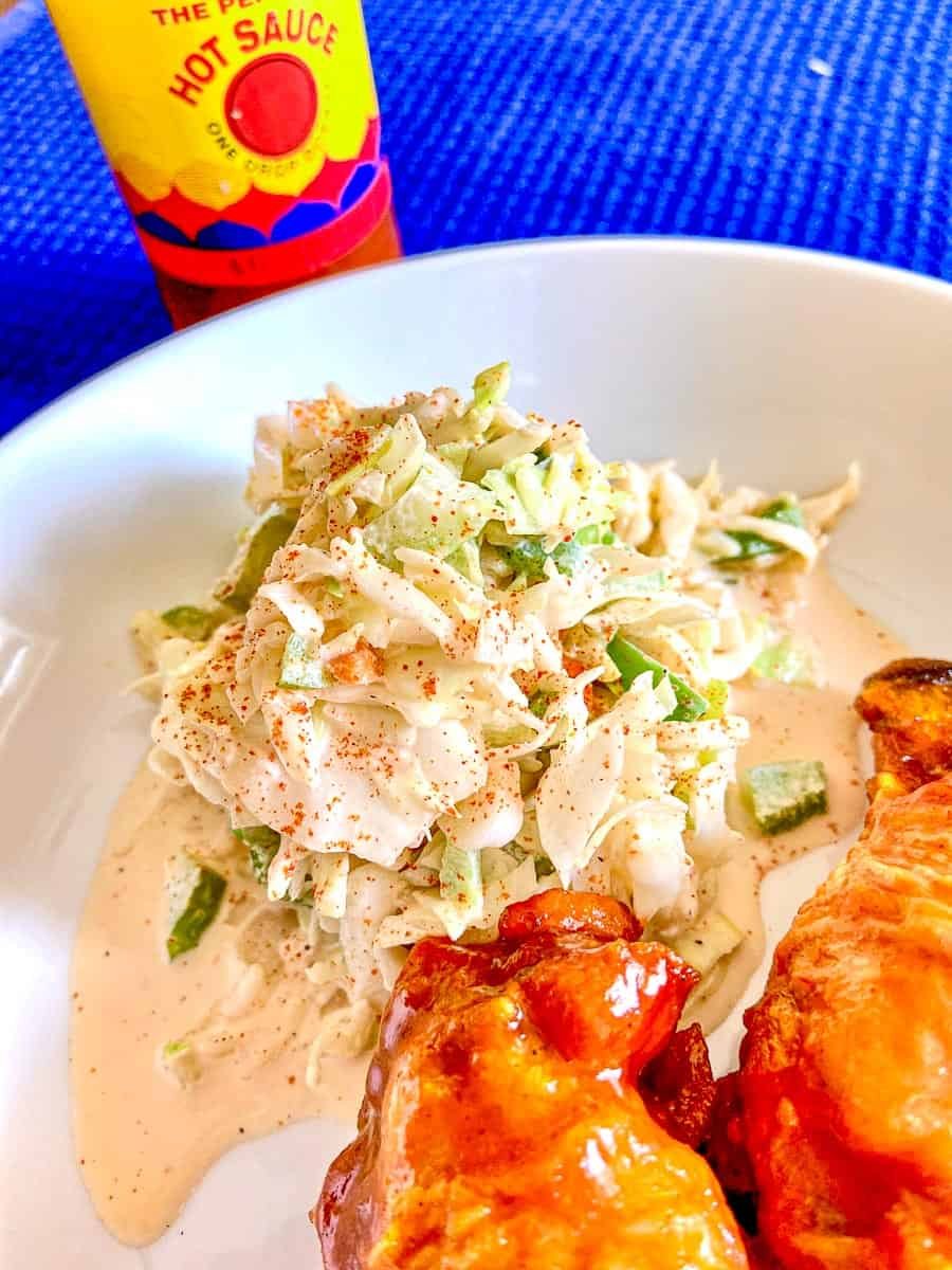 Creamy Creole Coleslaw on white plate with chicken wings