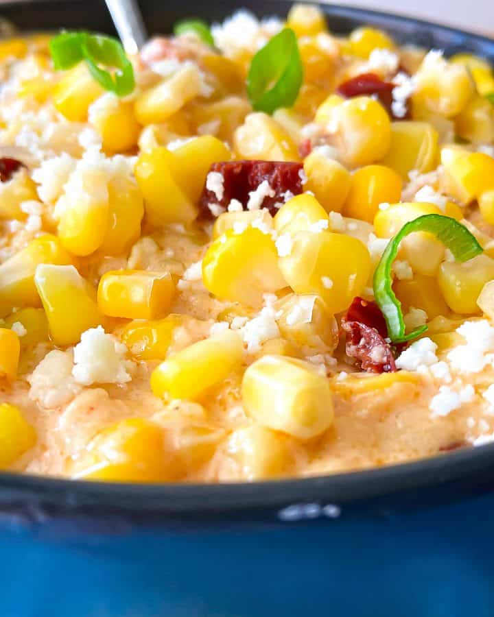 Corn Casserole in black dish garnished with green onion and crumbling cheese