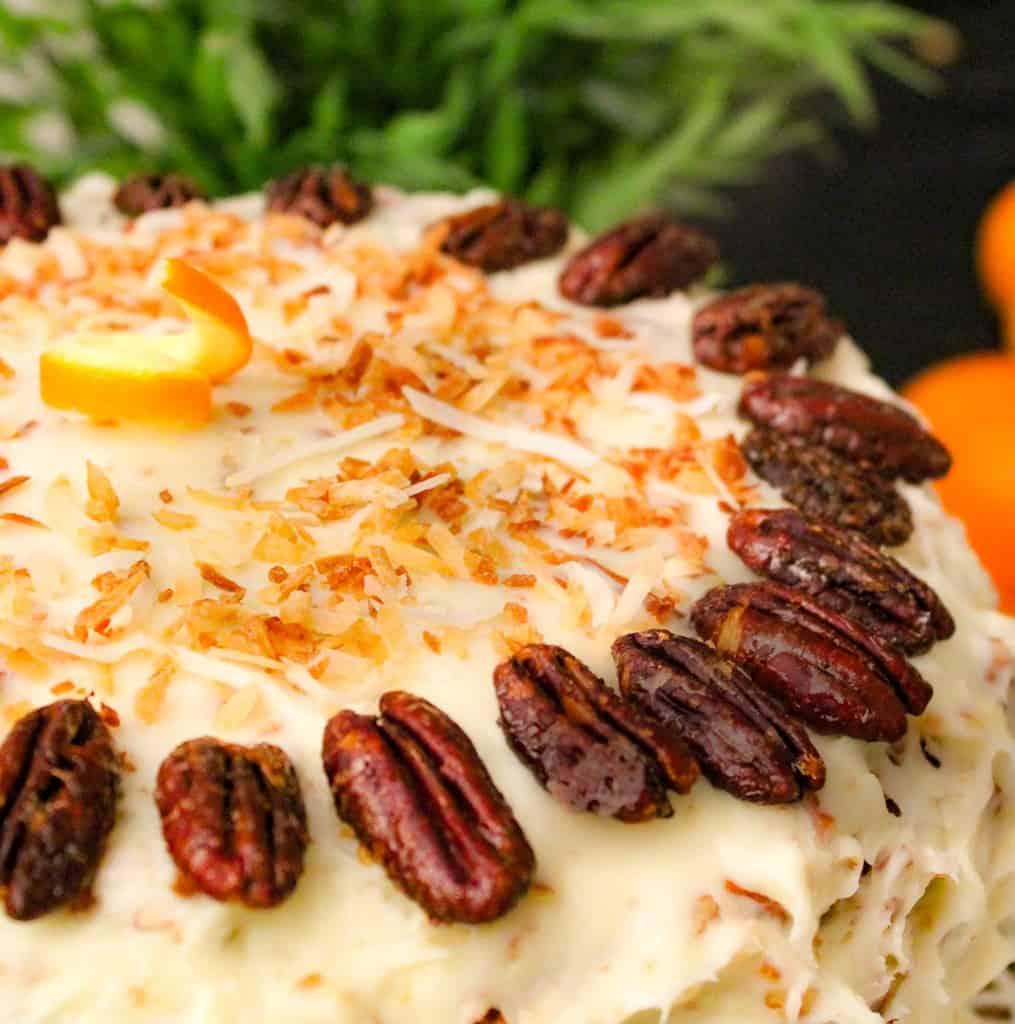 Orange Italian Cream Cake on cake plate with oranges in the background