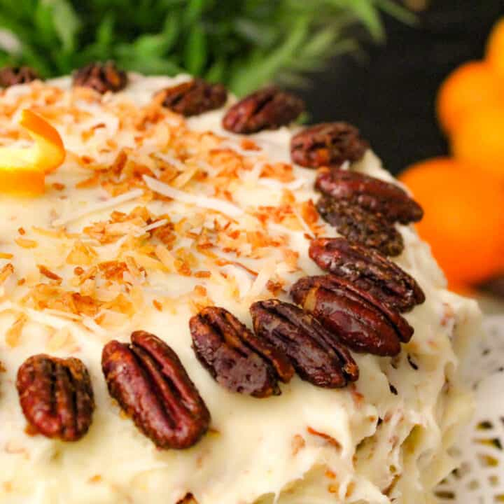 Orange Italian Cream Cake garnished with pecan halves and toasted coconut