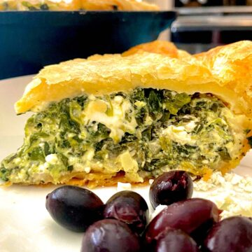 Slice of spinach feta pie on white plate with kalamata olives and feta crumbles