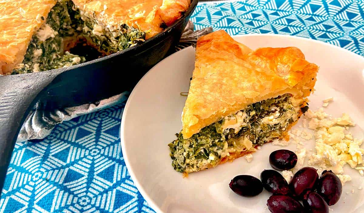 Slice of spinach feta pie on white plate with a side of kalamata olives.
