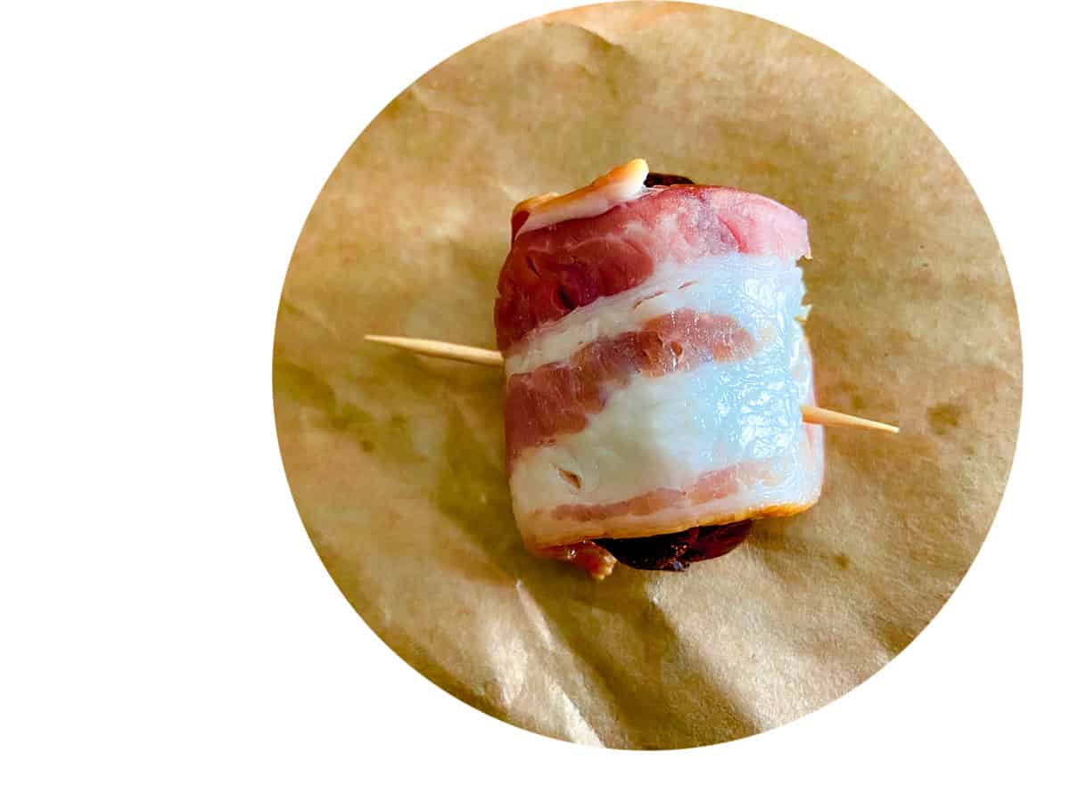 Bacon wrapped around stuffed date with toothpick in it