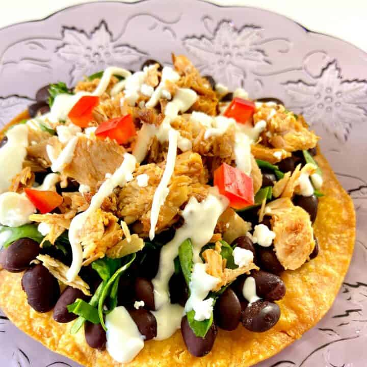 Adobo Chicken on corn tostada with black beans, cilantro and sour cream sauce