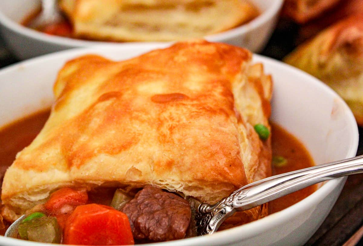 Beef stew in white bowl with a puff pastry on top
