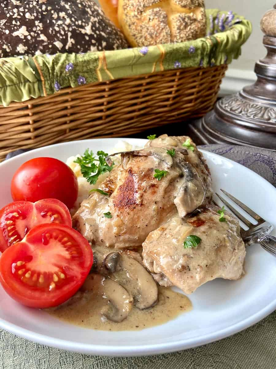 Chicken Fricassee on white plate with sliced cherry tomatoes