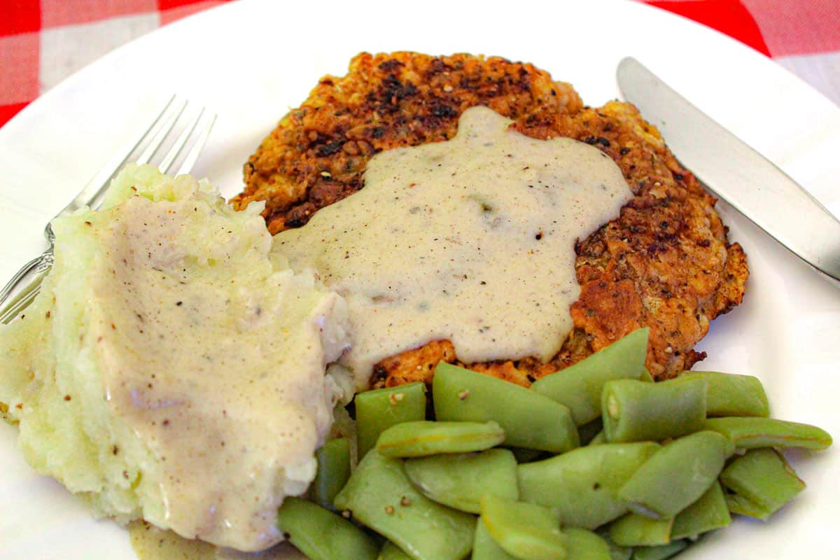 Mashed potatoes, green beans and chicken fried steak with cream gravy on white plate