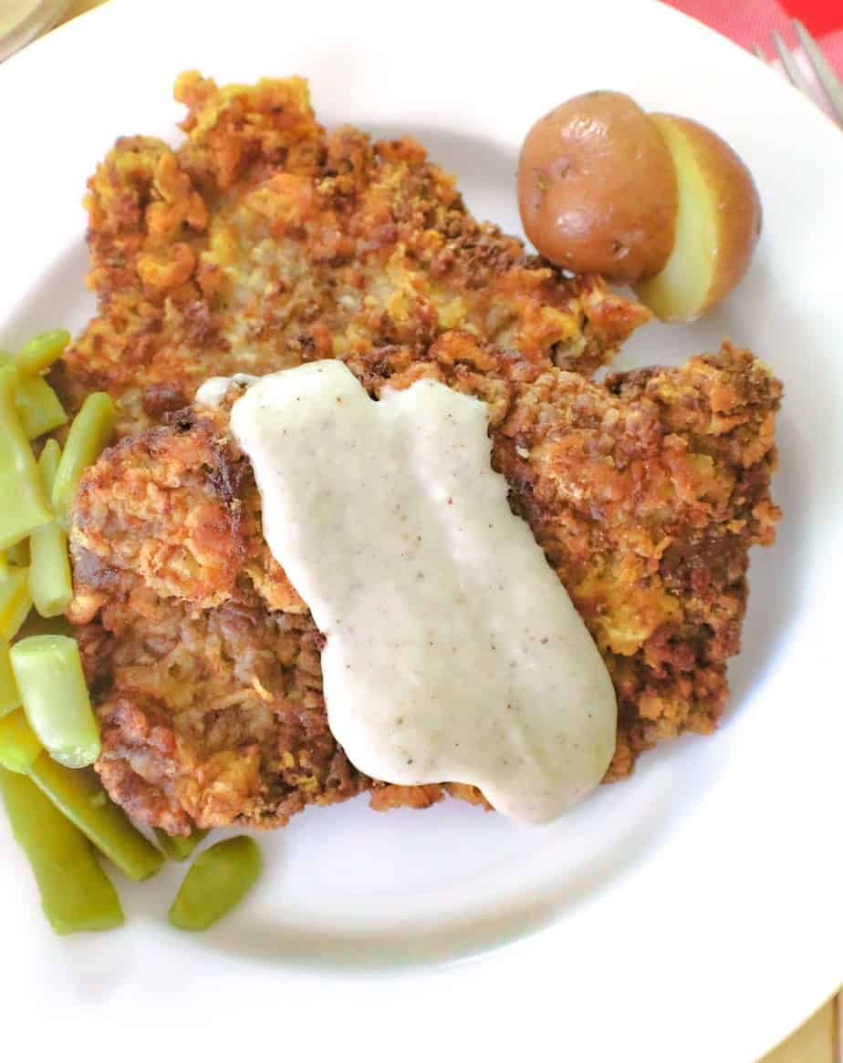 Chicken fried steak with cream gravy and a side of green beans
