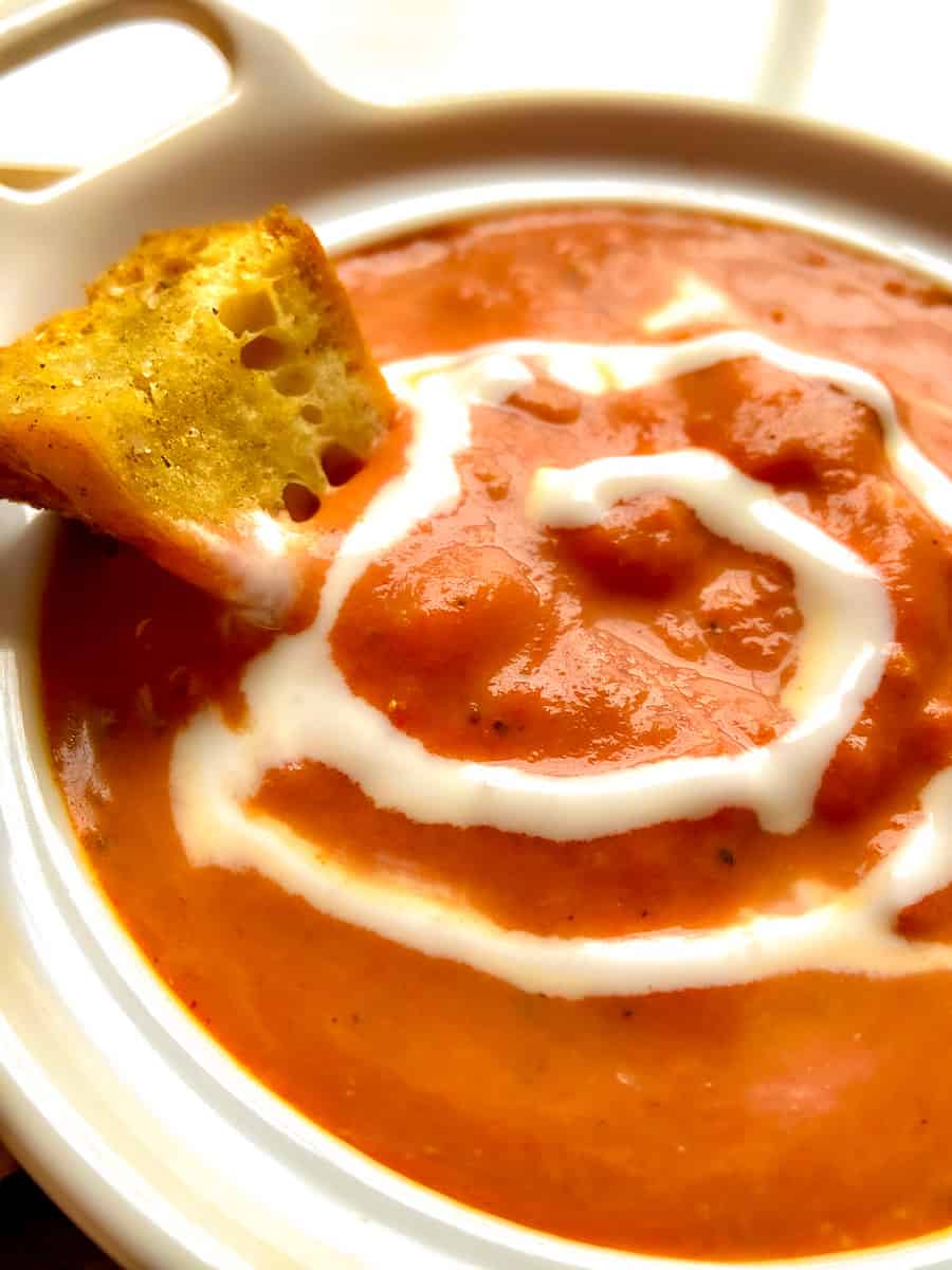 Smoked Tomato Bisque with crouton and a swirl of cream in white bowl.