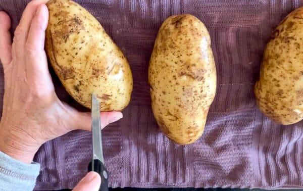 Paring knife cutting slits into russet potato