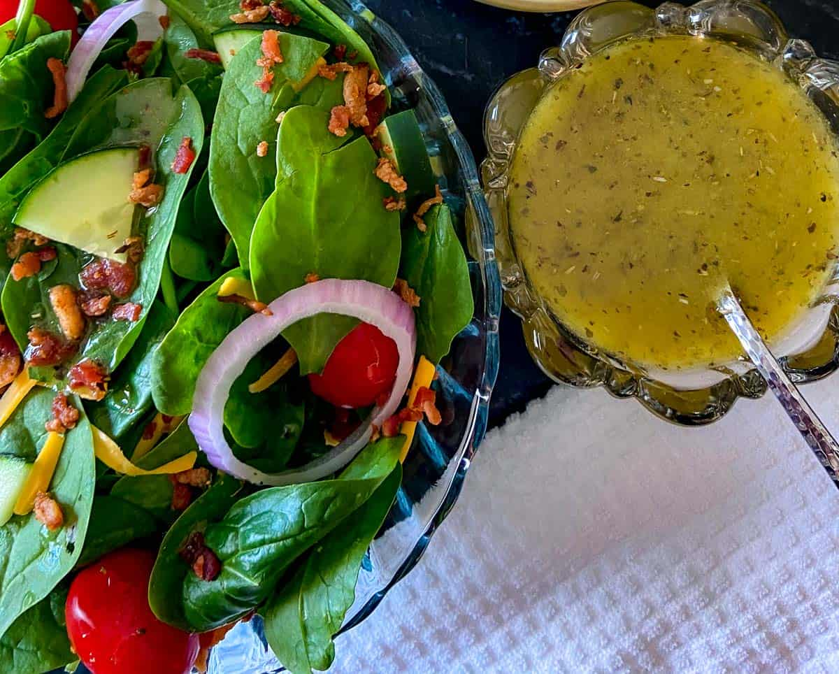 Spinach salad in a glass bowl with a side of White balsamic vinaigrette
