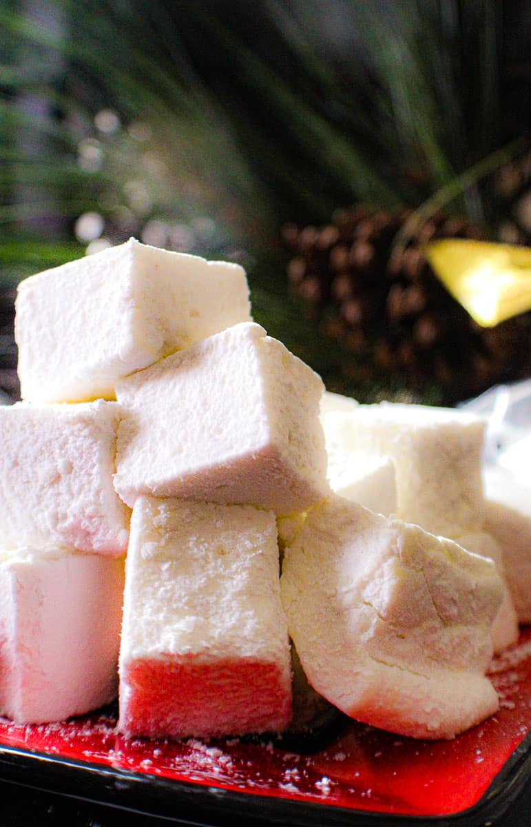 Homemade marshmallow squares stacked on a red plate