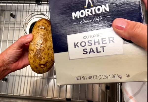 Kosher salt being sprinkled over oil raw potato