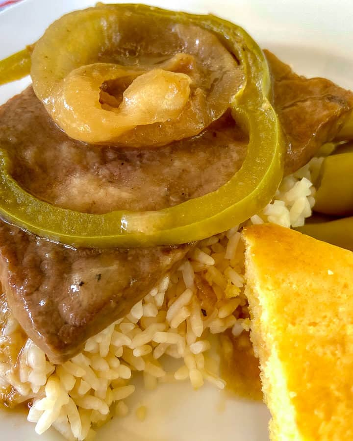 Smothered Steak with Brown gravy, onions and peppers over rice with a side of green beans and cornbread