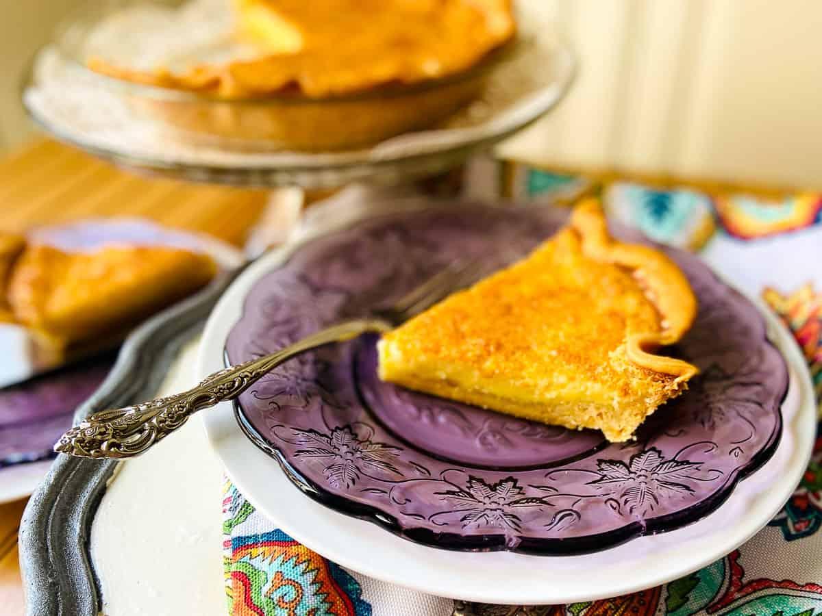 A slice of buttermilk pie on purple plate