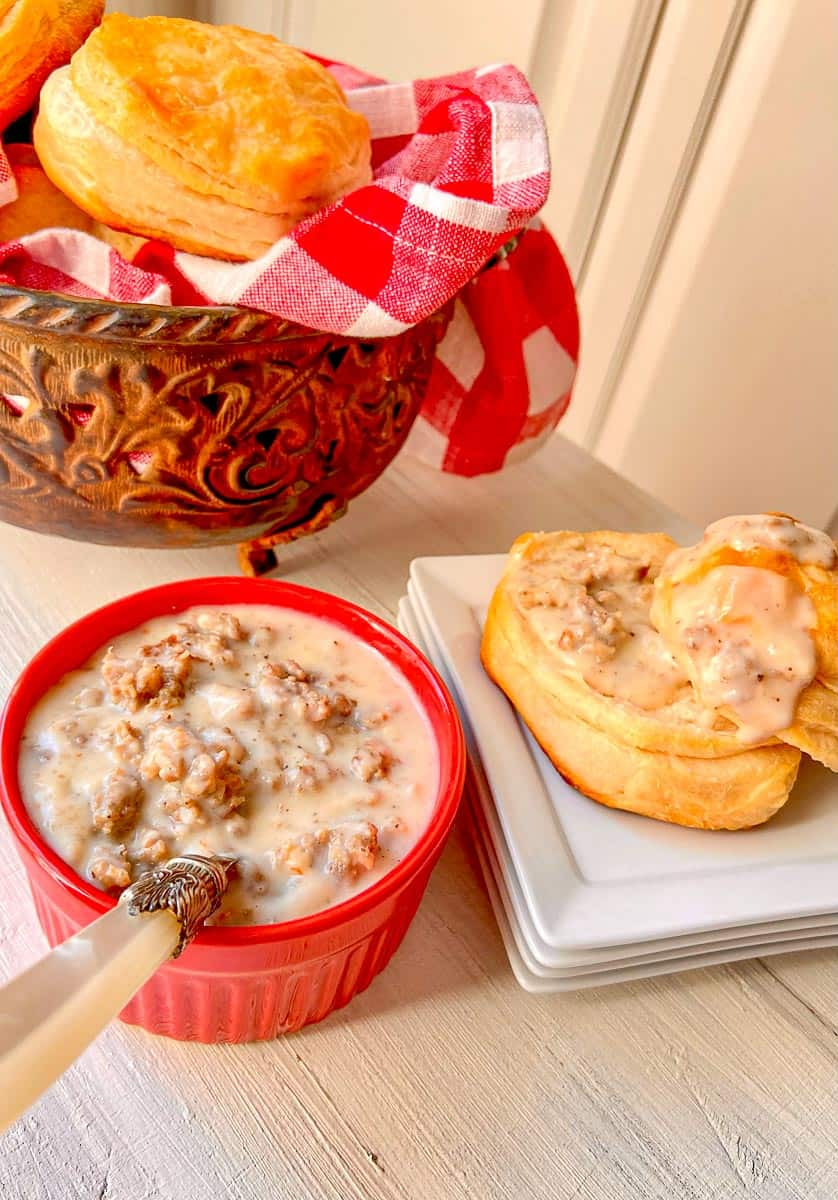 Sausage Cream gravy in a red bowl and drizzled over a flaky biscuit