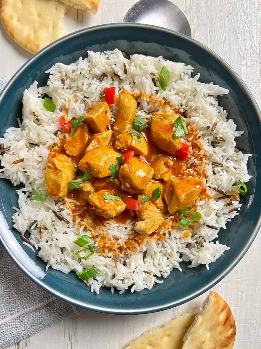 Butter Chicken with basmati rice in blue bowl