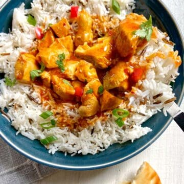 Indian Butter Chicken with basmati rice in blue bowl with serving spoon