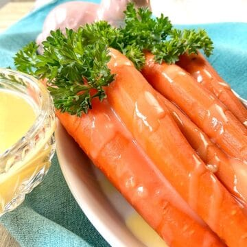 Orange glazed carrots in white bowl