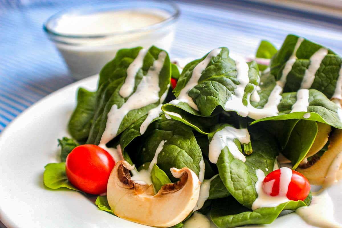 Buttermilk Dill Ranch Dressing on spinach greens with cherry tomatoes and mushroom slices