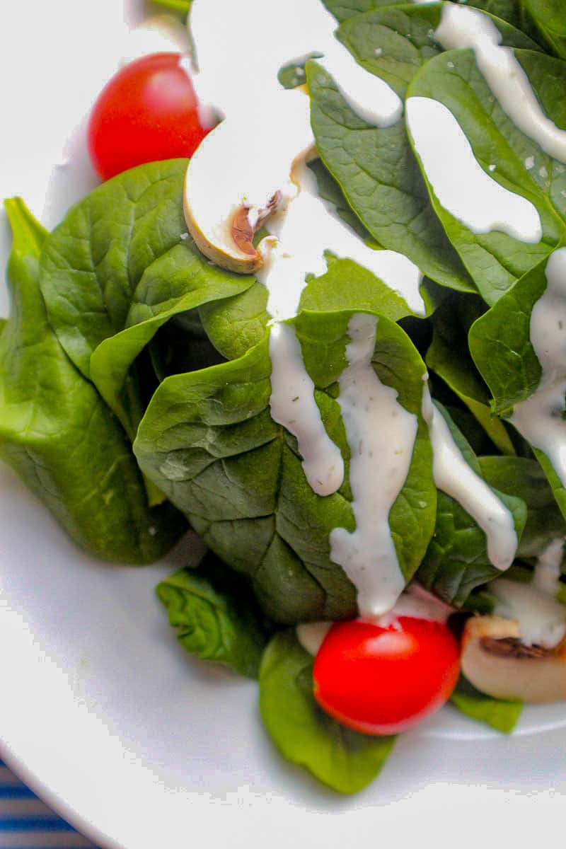 Buttermilk Dill Ranch dressing drizzled over spinach greens