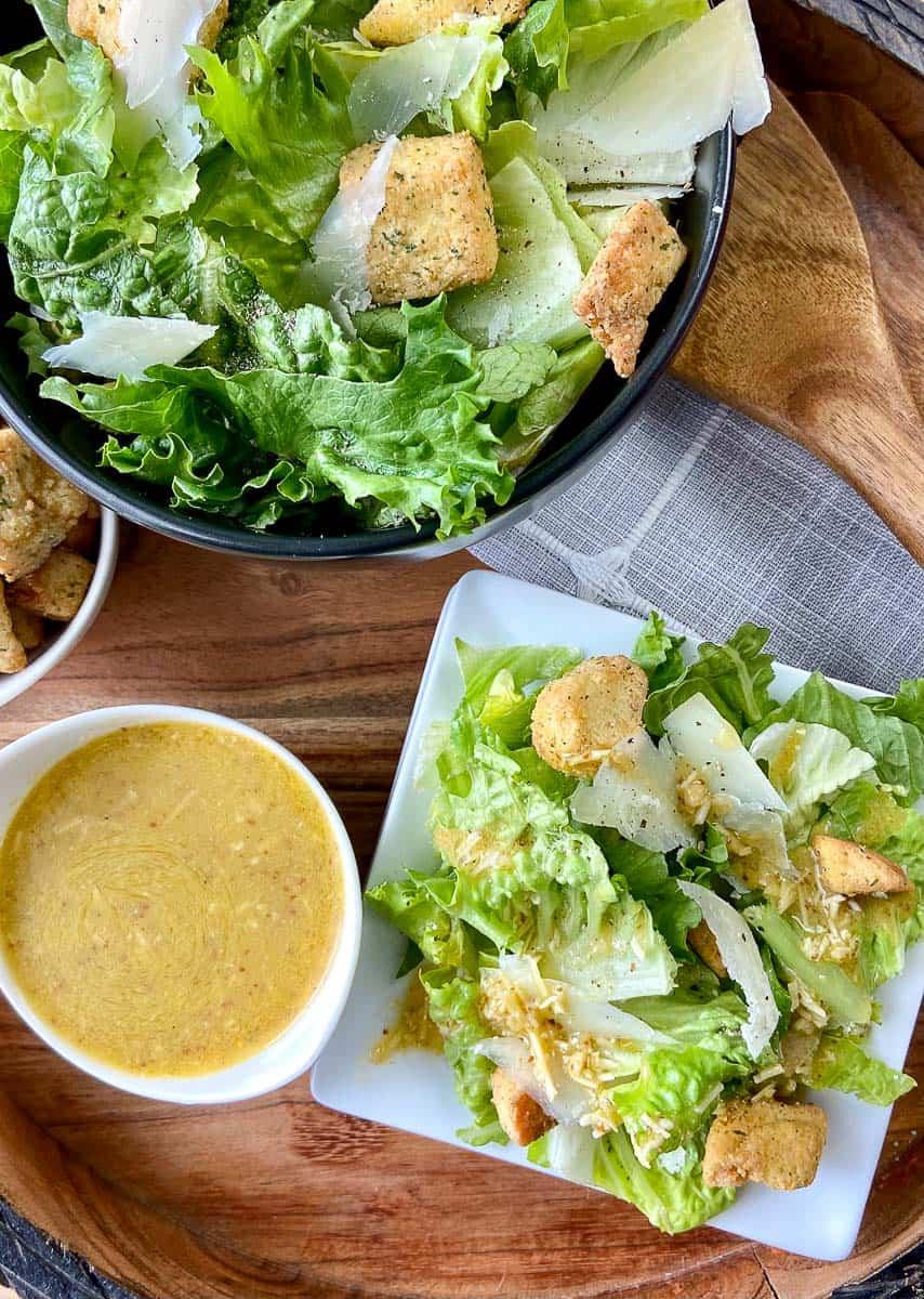 Caesar salad dressing in a bowl next to salad.