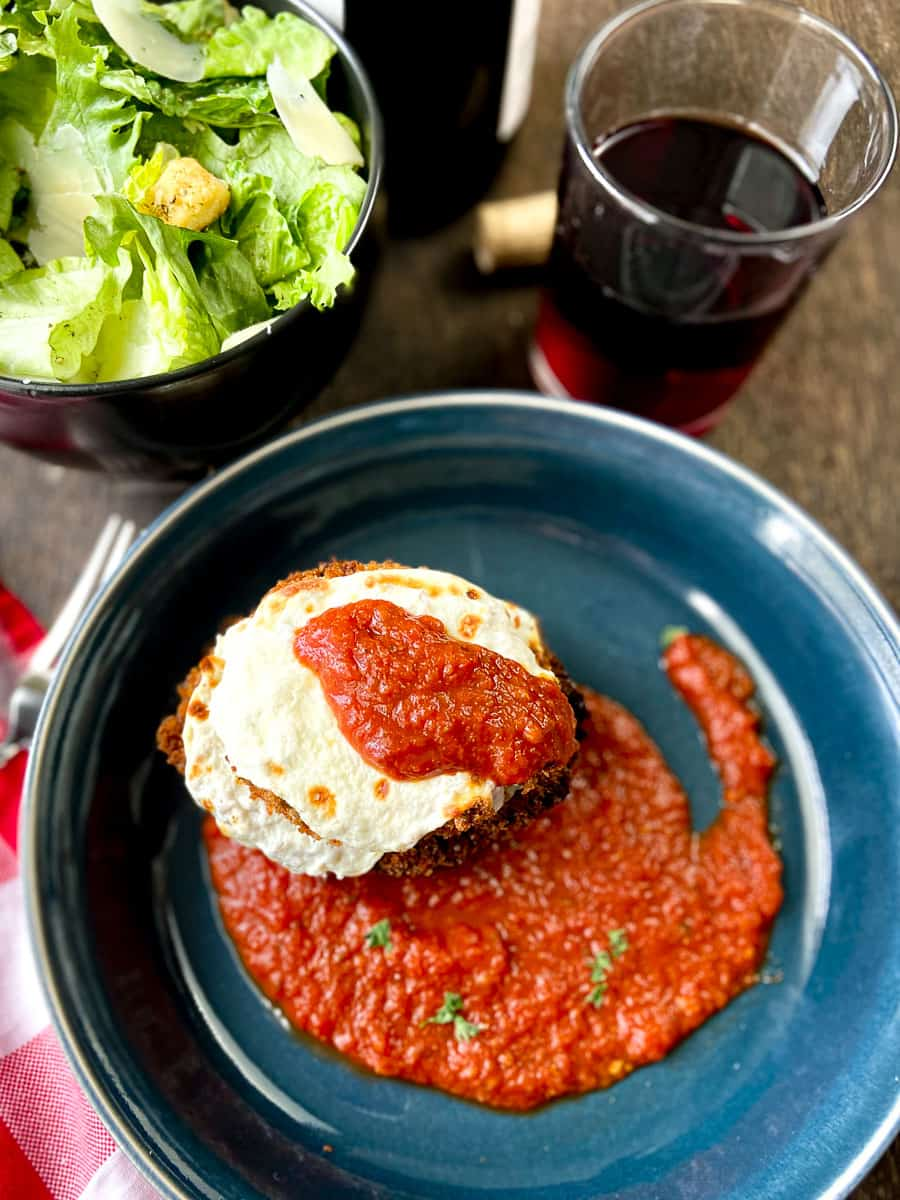 Crispy fried eggplant parmesan in blue dish drizzled with pasta sauce