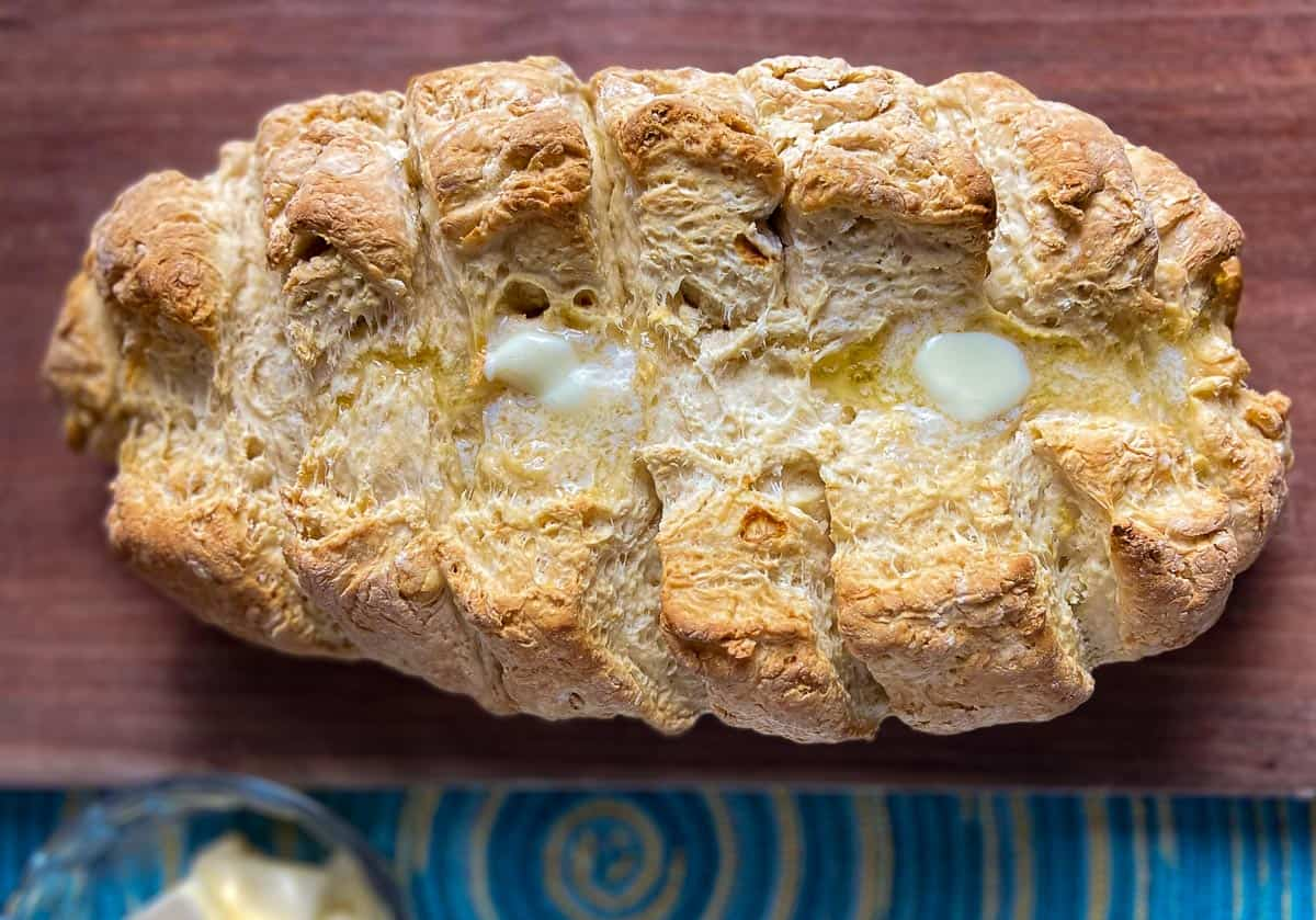 Loaf of soda bread topped with butter on wooden cutting board