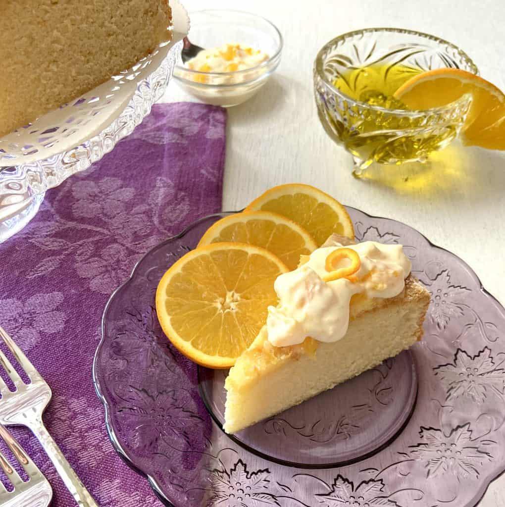 Slice of orange olive oil cake on purple plate with sliced oranges.