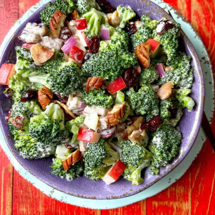 Broccoli Crunch Salad in purple bowl on red wooden table