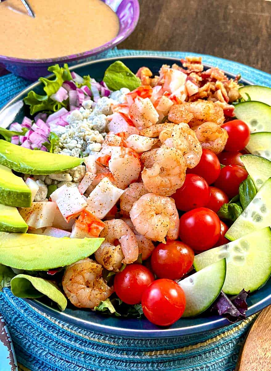 Seafood Cobb Salad in a shallow blue bowl with dressing on the side