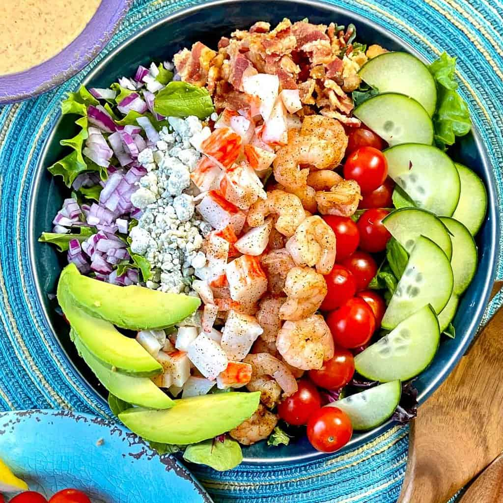 Seafood Cobb Salad with ingredients in rows on top of mixed greens