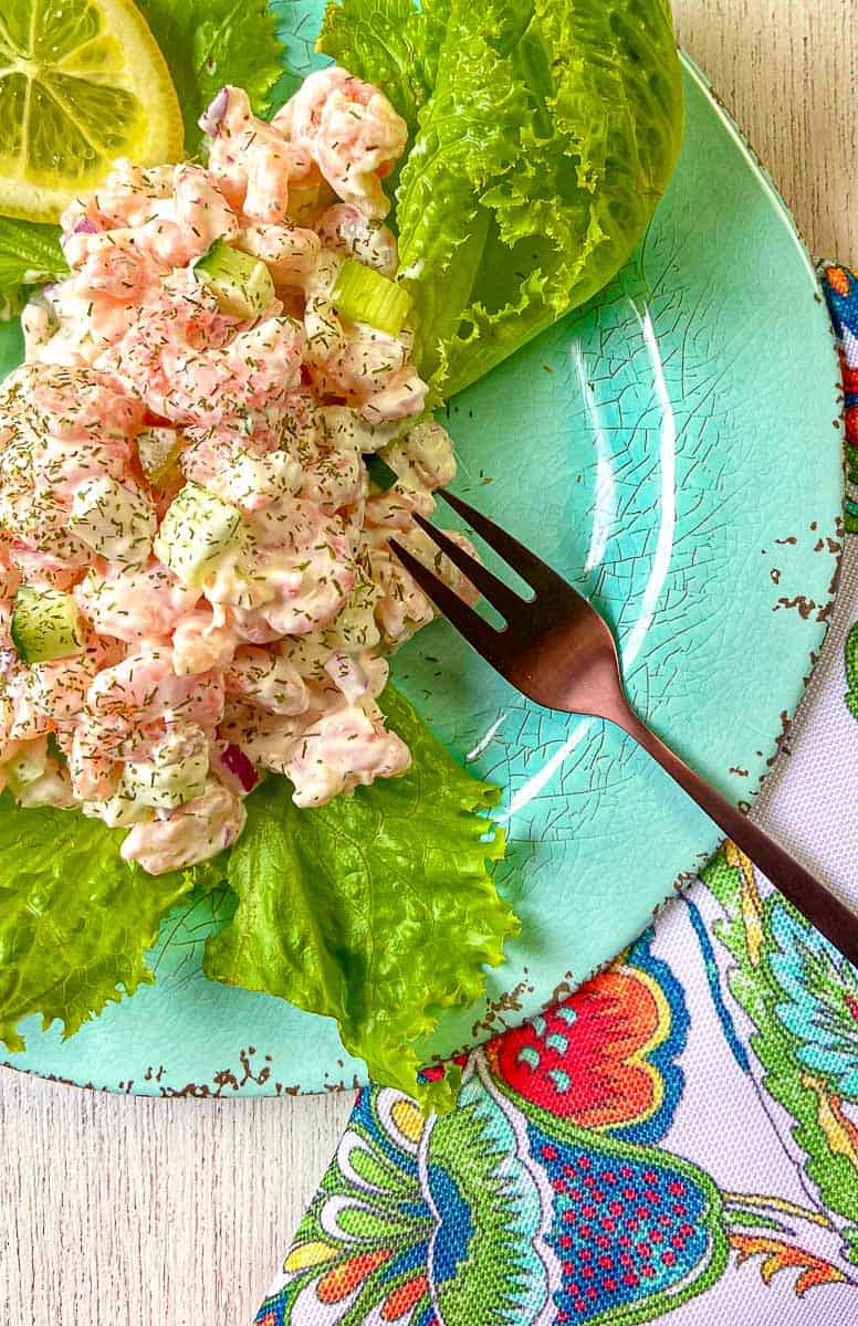 Cold Dill Shrimp Salad on lettuce greens on turquoise plate