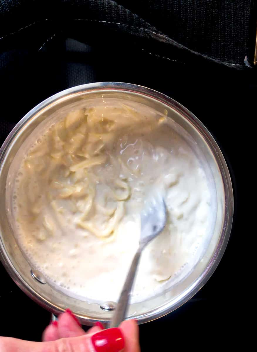 Sour cream sauce being stirred in saucepan.