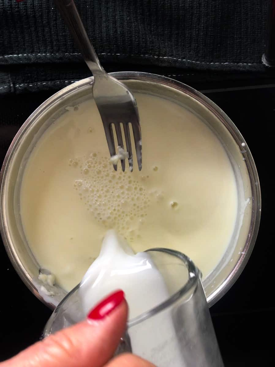 Slurry being poured into saucepan with cheese.