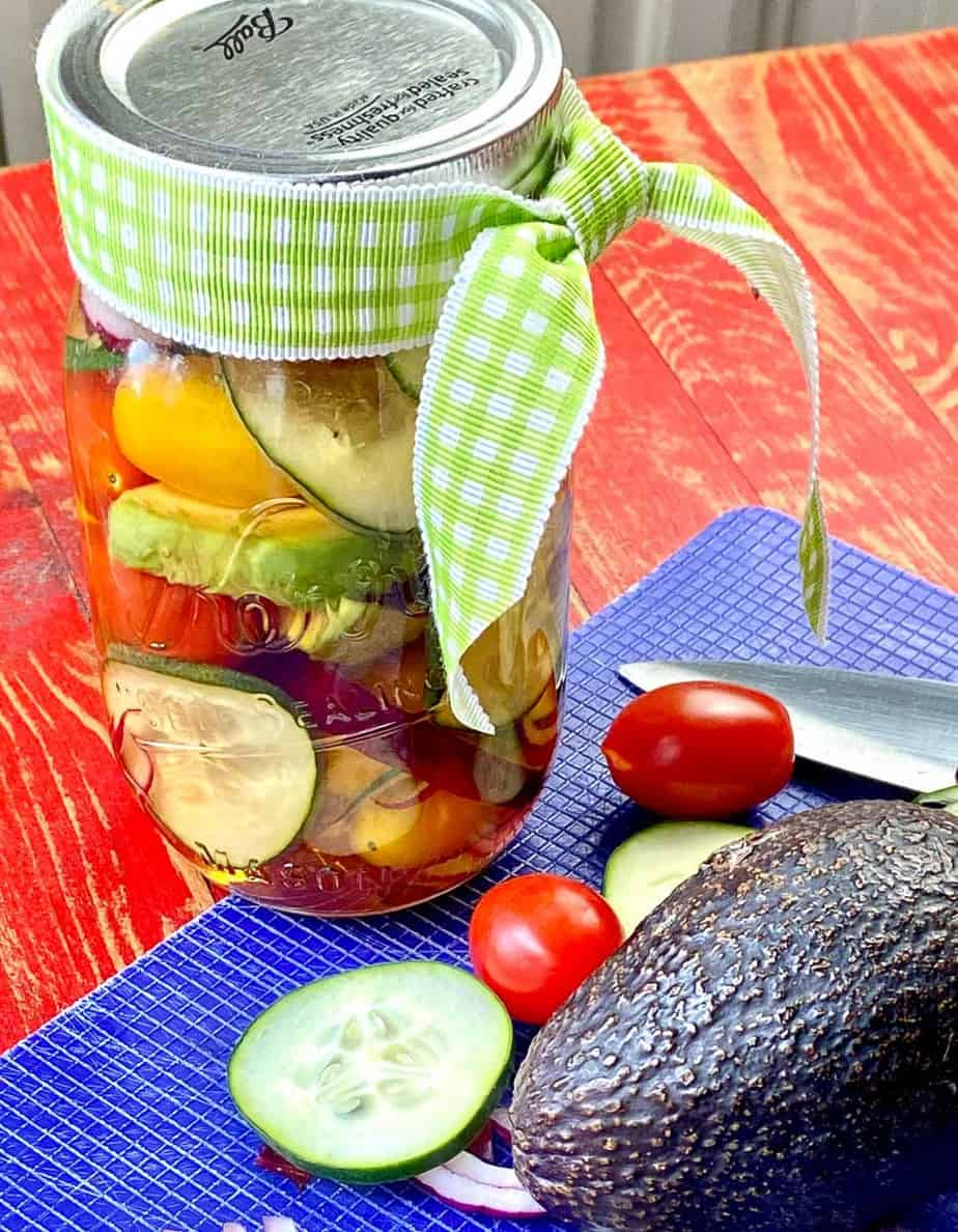 Marinated cucumber, onion and tomato in mason jar with green plaid bow as hostess gift.