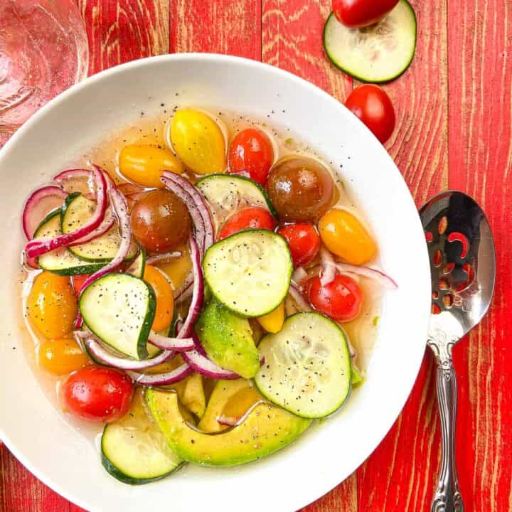 White bowl of marinated vegetable salad.
