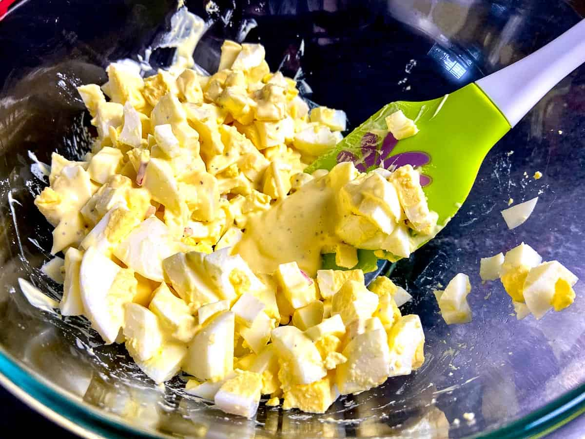 Dressing being folded into egg salad with spatula.