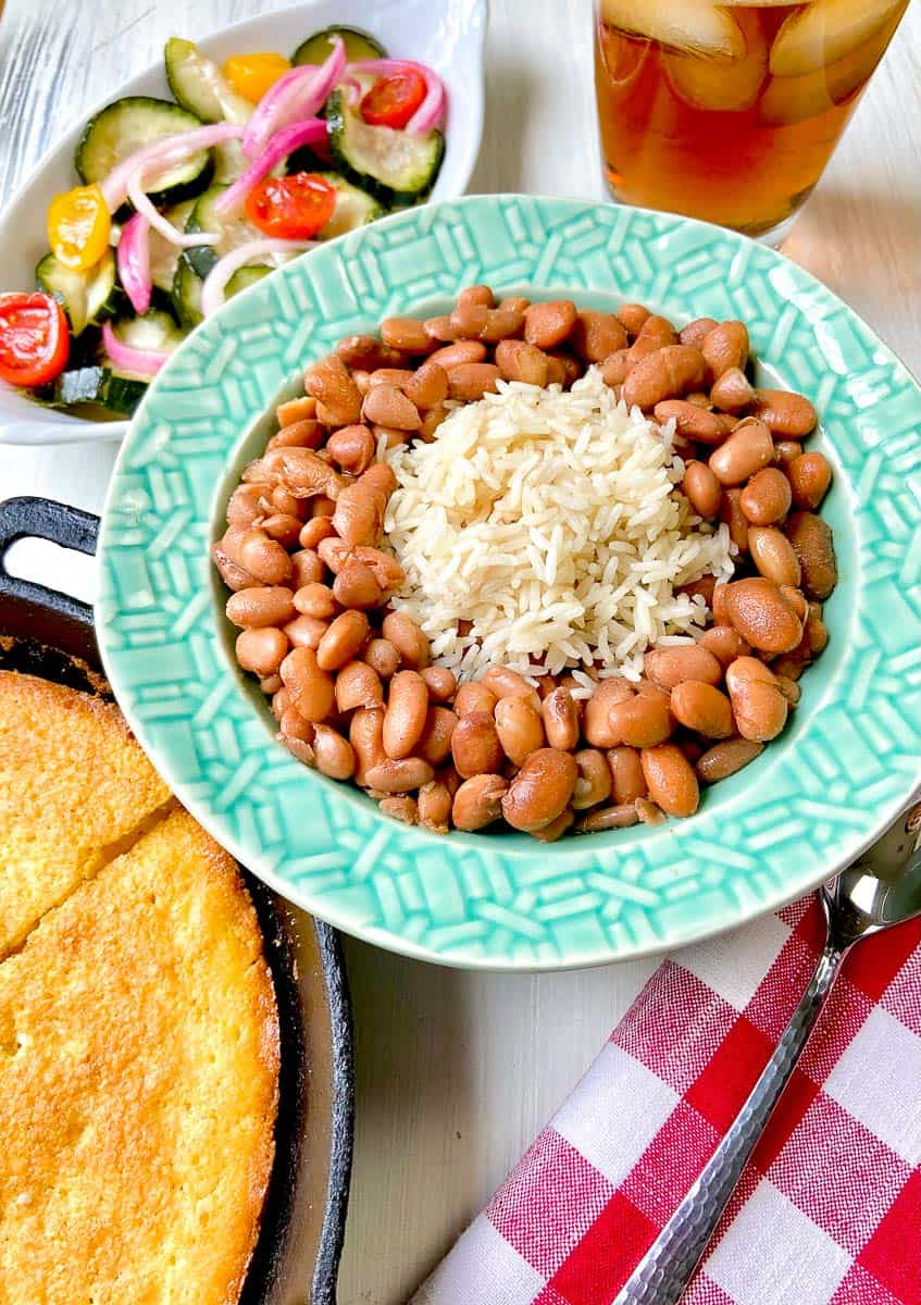 Pinto beans and rice in turquoise bowl on table.