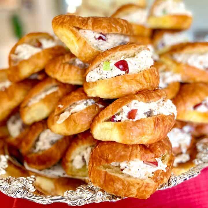 Chicken salad sandwiches on mini croissants stacked on silver platter.