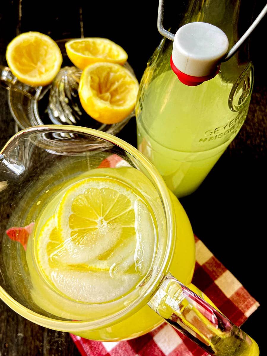 Lemonade in pitcher garnished with ice cubes and lemon slices.