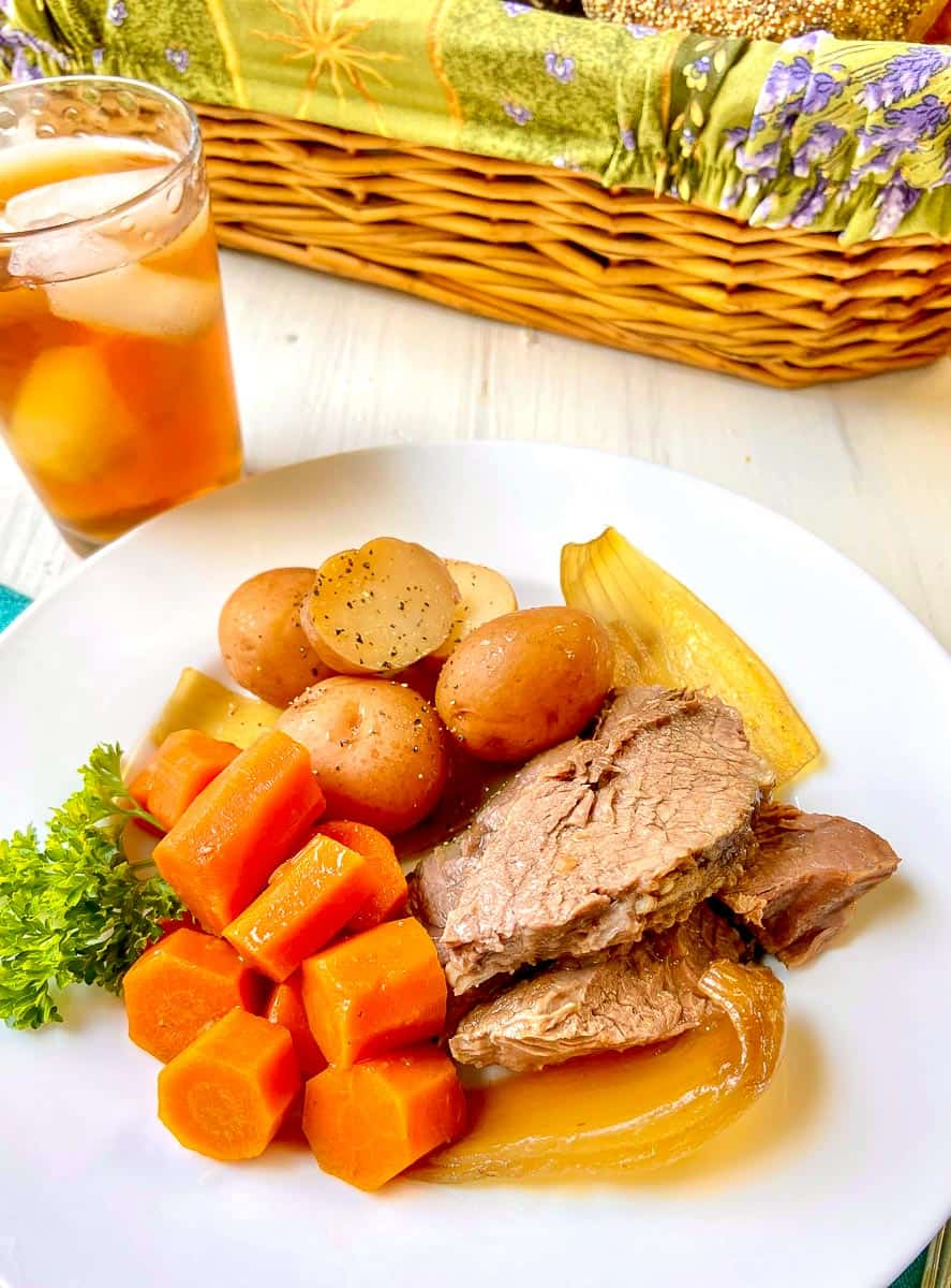 Pot roast with carrots, potatoes and onions on white plate.