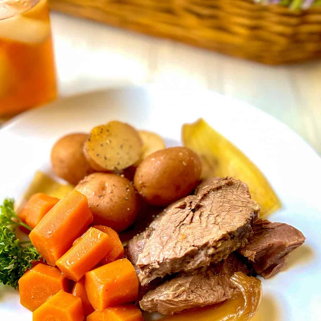 Sliced roast with onions, carrots and potatoes on white plate.